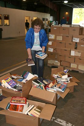 "PAULA FORTNER, assistant librarian at Norwood Schools, looks through some of the boxes of books made available to area school districts free of charge through the Christian Appalachian Project's ""Operation Sharing"" program.  The Corbin, Ky.,-based non-profit organization has teamed up for the past 15 years with Missouri State University-West Plains to provide much needed books and resources to school and public libraries in southern Missouri.  (Missouri State-West Plains Photo)"