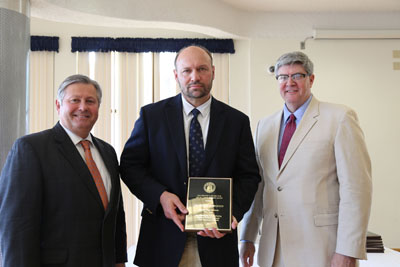 DR. PHILLIP HOWERTON, center, associate professor of English at Missouri State University-West Plains, received the Governor's Award for Excellence in Education during an April 13 luncheon in Jefferson City, Mo. With him are Missouri State-West Plains Chancellor Drew Bennett, left, and Missouri Associate Commissioner of Higher Education Rusty Monhollon. (Photo provided)