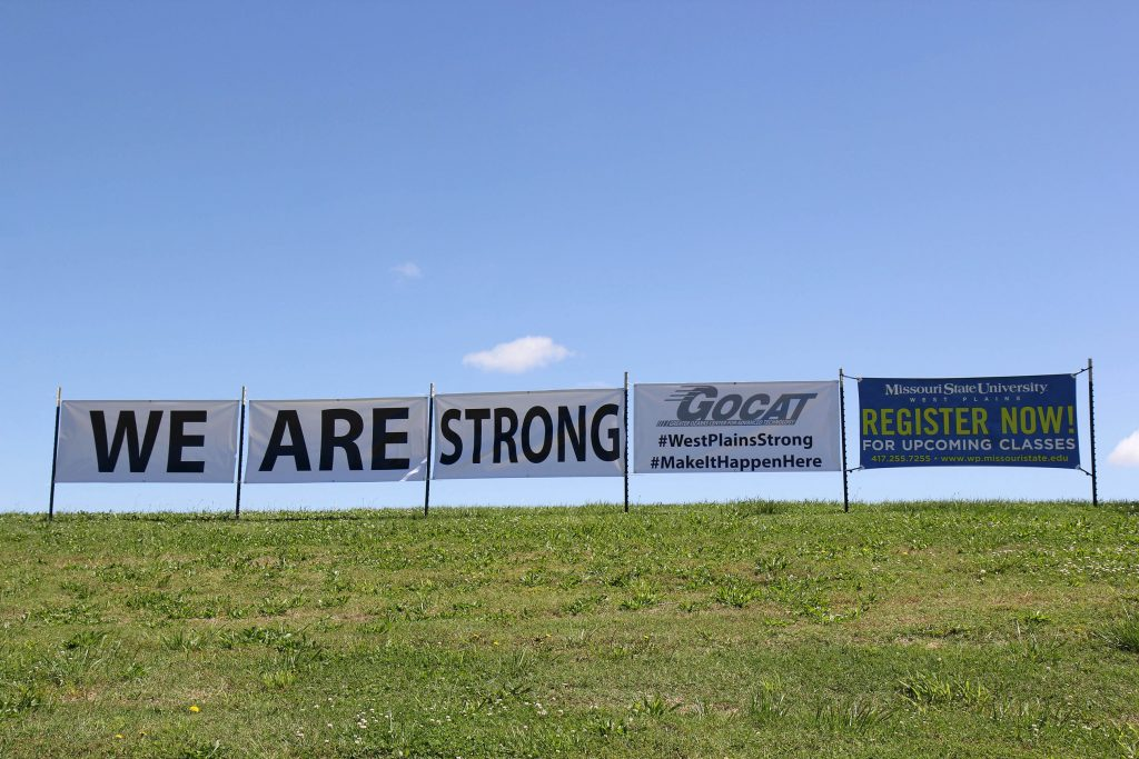 WE ARE STRONG – Officials with the Greater Ozarks Center for Advanced Technology (GOCAT) are showing their resilience with these banners along Broadway near the facility on Howell Avenue in West Plains. Despite devastating flooding in April, training programs offered at the facility will be up and running in time for the fall semester, which begins Aug. 21, they said. (Missouri State-West Plains Photo)