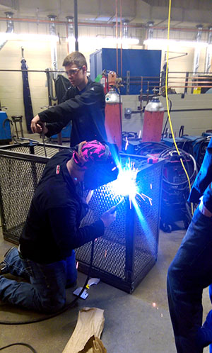 Students welding a cage.
