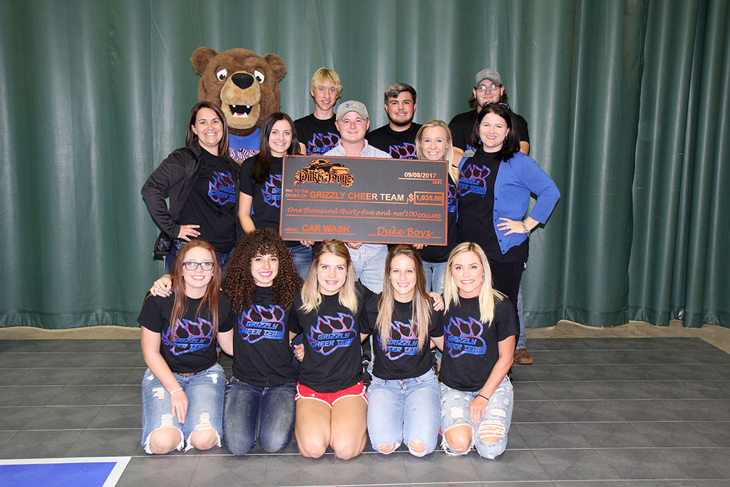 A TOTAL OF $1,035 was raised for the Missouri State University-West Plains Grizzly Cheer team during a customer appreciation day and fundraiser hosted by the Duke Boyz on July 15. In addition to hosting rides and food to celebrate three years in business, organizers with the Duke Boyz donated 75 percent of the proceeds from car washes conducted by the cheer team and T-shirt sales as part of the event. The money will be used to purchase new uniforms. On hand for the check presentation were, front row from left, cheer team members Tori Terrill, Mtn. View; Carlea Badolian, West Plains; Alexis Fuwell, Mountain Grove; Neely Gobel, West Plains; and Felicity Snelling, Licking. Second row: Assistant Coach Keena Simpson; cheer team member Makayla Koon, West Plains; Duke Boyz owner Kyle Duke; cheer team member Karli Habel, Spokane; and cheer team coordinator Rachel Peterson. Back row: Grizz (aka Robyn Rex, Spokane); and cheer team members Zachary Cook and Brandon Owens, both of West Plains; and Jayse Muncy, Dadeville. (Missouri State-West Plains Photo).