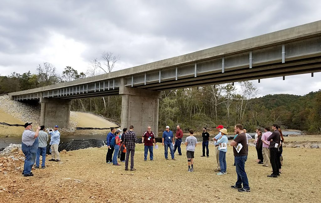 SEVERAL OF THOSE ATTENDING the American Association of Geographers-West Lakes Division (AAG-WLD) annual meeting gathered with Missouri State University Distinguished Professor Dr. Robert Pavlowsky near the new Highway CC bridge over the North Fork River to discuss global warming and its effects on flooding in the Missouri Ozarks. The original bridge, which stood over 40 feet above the river, was washed away by flash flooding in April this year. (Photo provided)