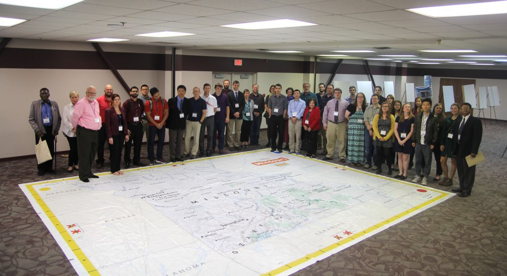 MANY OF THOSE ATTENDING the American Association of Geographers-West Lakes Division (AAG-WLD) annual meeting Oct. 19-21 in West Plains took a few moments to pose by this 21-by-17-foot geographic map of the state of Missouri that was on display courtesy of the Missouri Geographic Alliance. (Missouri State-West Plains Photo)