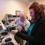 A student receives help with an electronic circuit board from an instructor.