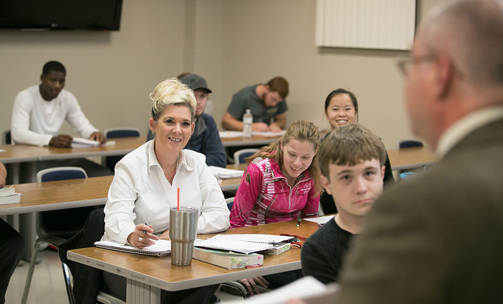Students sitting in a lecture class smiling at the teacher.