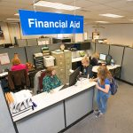Students fill out paperwork at financial aid desk.