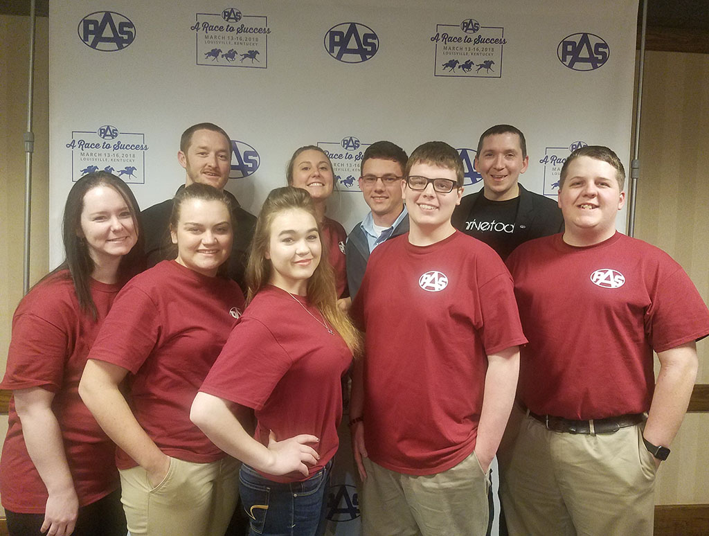 A group of students are standing by row in front of a banner at a national agriculture conference. SEVEN STUDENTS from Missouri State University-West Plains Postsecondary Agriculture Students (PAS) Organization attended the 2018 National PAS Conference and Convention in Louisville, Kentucky. Front row from left, Dessa McBride, Haden Garrett, Sabrina Brinkerhoff and Jarod Coatney, all of West Plains, and Douglas Cooley, Plato. Back row: PAS National Vice President Asa Nelson; Missouri State-West Plains PAS members Jerica Will, Winona, and Bryce King, Alton; and conference speaker Mark Jewell of Mark Jewell Speaking and Training. (Photo provided)
