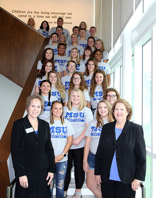 The Student Ambassadors stand by row on a staircase in Gohn Hall.