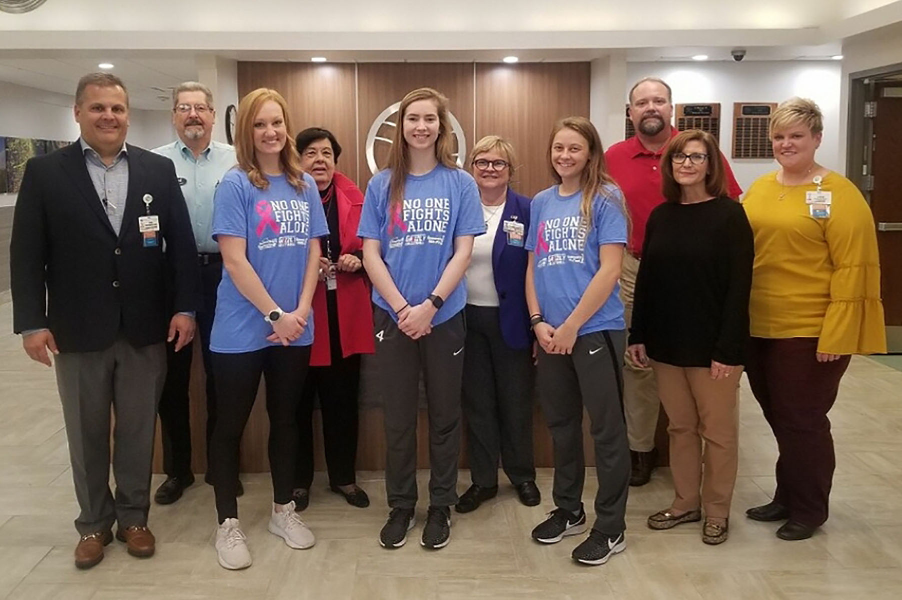 A group of people representing Ozarks Medical Center, Community First Banking Company and Grizzly Volleyball stand in a row in the OMC lobby. The volleyball representatives are wearing the T-shirts being sold for the fundraiser.
