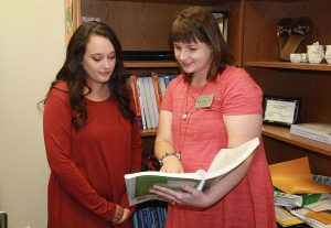The student and instructor look through a textbook while standing in the instructor's office.