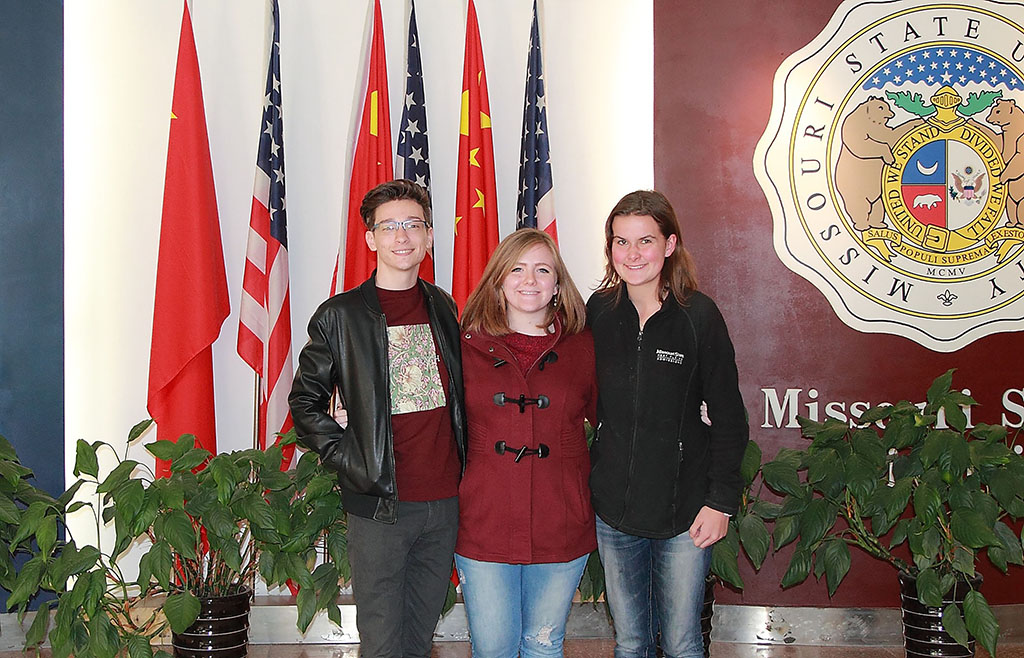 The students stand in front of the American and Chinese flags and university logos at the campus in China.