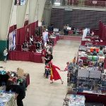 A bird's eye view of the West Plains Civic Center arena with various vendor booths and people at the 2018 Oz-Con convention.
