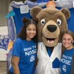 Two students with faces painted for homecoming stand with the Grizzly mascot in front of a blue backdrop.