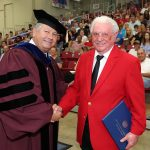 Chancellor Bennett shakes Jack McNevin's hand in congratulations.