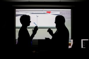 A student and teacher stand silhouetted in front of a screen showing a scene from a video game.