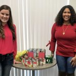 The two ladies stand next to a table with several canned good items sitting on it.