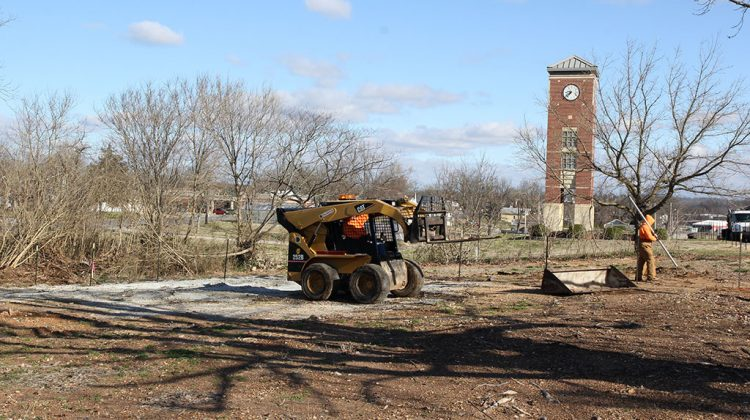 A man driving a small bulldozer and another man set posts for a fence. In the background is the campus' bell tower.