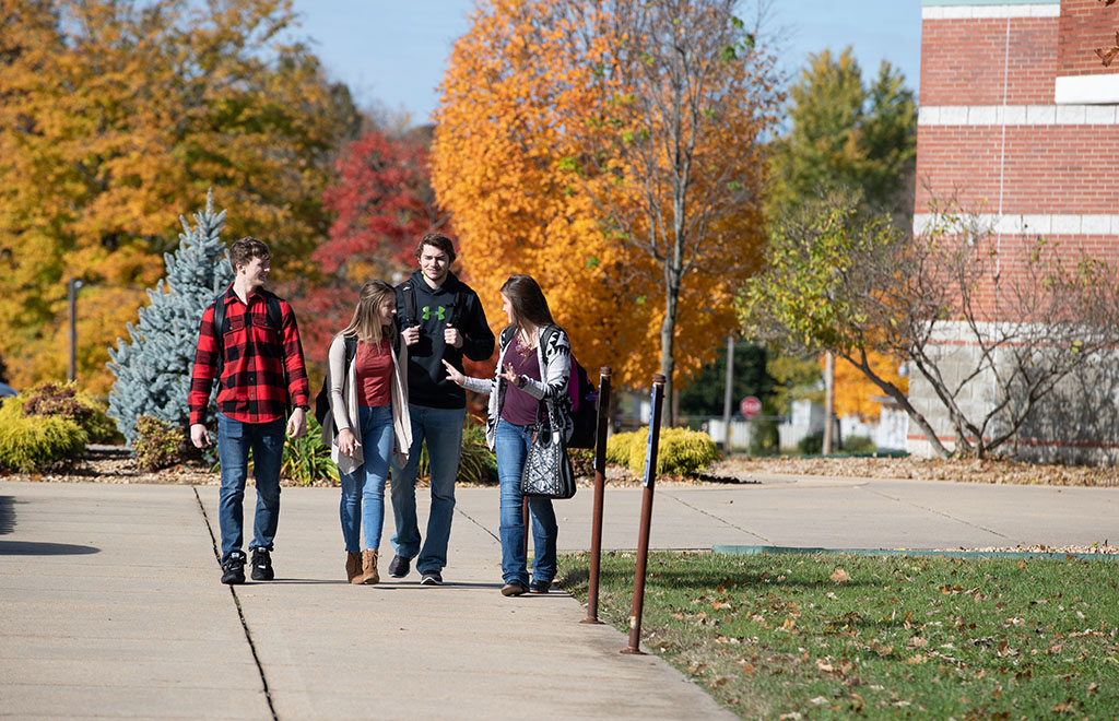 Students walk in a group along a sidewalk outside a classroom building