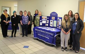 The group stands in rows next to a table with information about Health Information Technology.