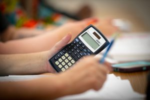 A close-up view of a student holding a calculator in class.
