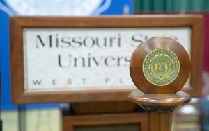 The commencement mace stands in front of the university podium.