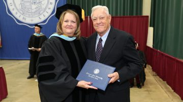 Two people stand next to each other holding an engraved diploma folder.
