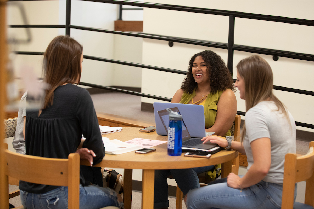 Three students are sitting around a table talking and studying with their books and laptops.