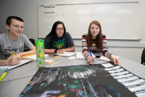 Students seated around a table in a classroom discuss a poster that is part of a class project.