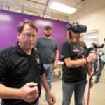 An instructor shows a student wearing goggles and holding a spray paint gun how to use the virtual reality computer program.