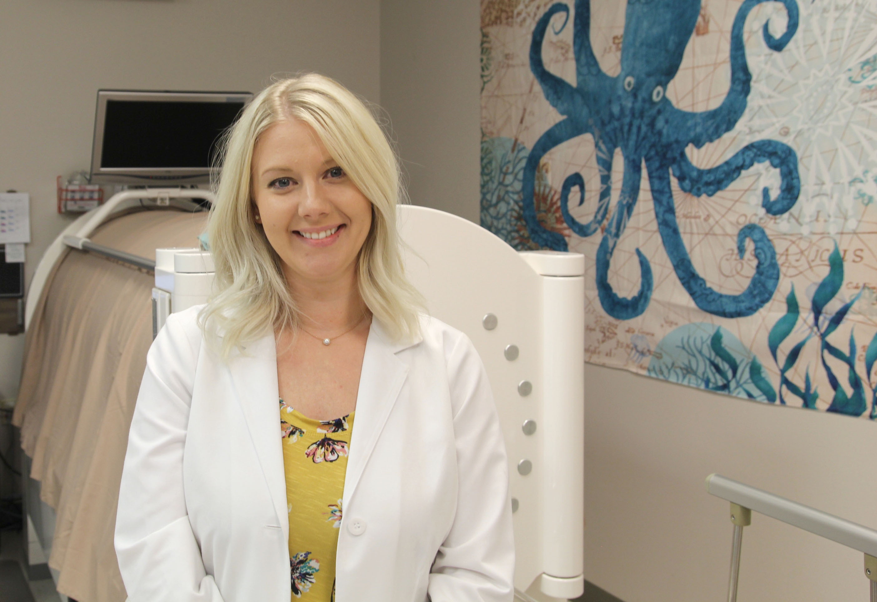 Lynsey Sullivan stands in front of a machine at her workplace. A blue octopus is painted on the wall on the right side of the image.
