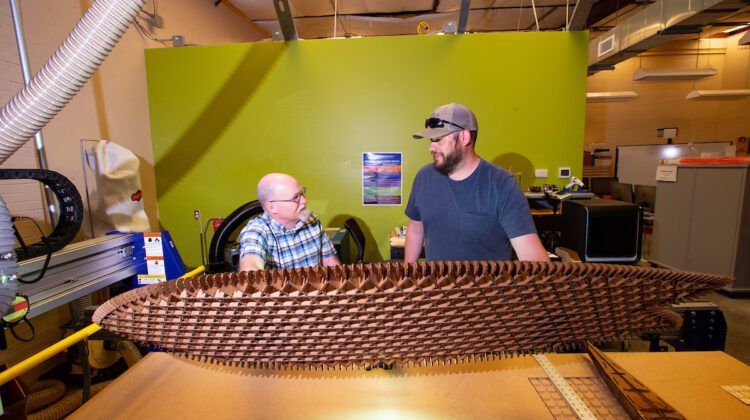 Teacher and student stand behind a piece of equipment and hold up a large lattice plank created on the machine.