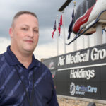 A man stands outside in front of a sign that says Air Medical Group Holdings and Air Med Care. On top of the sign are flags from different states and a medical helicopter.