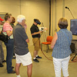 A group of people are gathered around a man wearing virtual reality goggles while pointing a paint gun at a big screen TV.