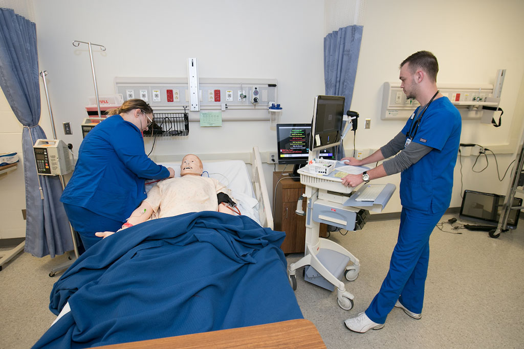 Nursing students work on equipment in the simulation lab.