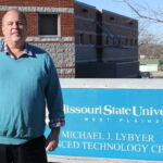 Dr. Birdyshaw outside Lybyer with sign