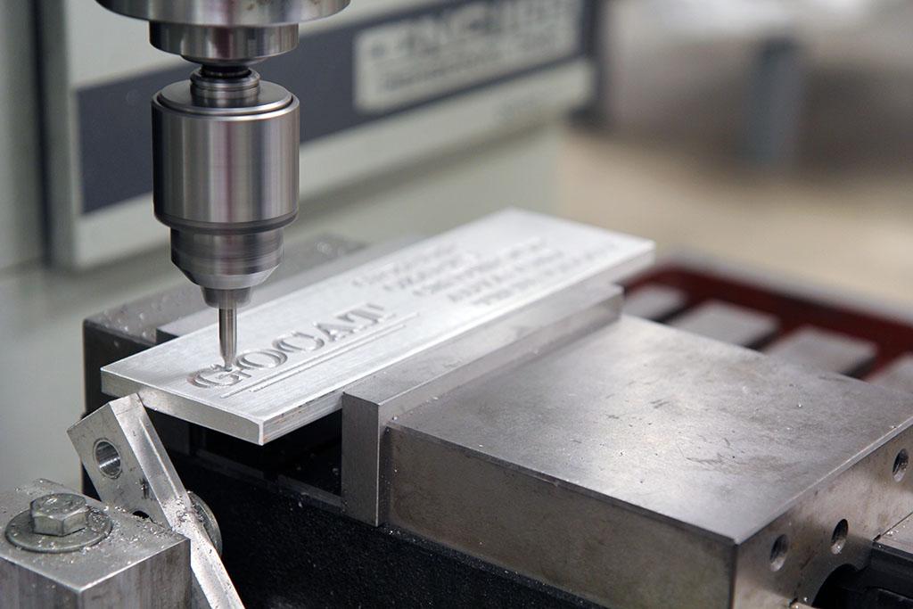 A machine spells out GOCAT on a piece of metal